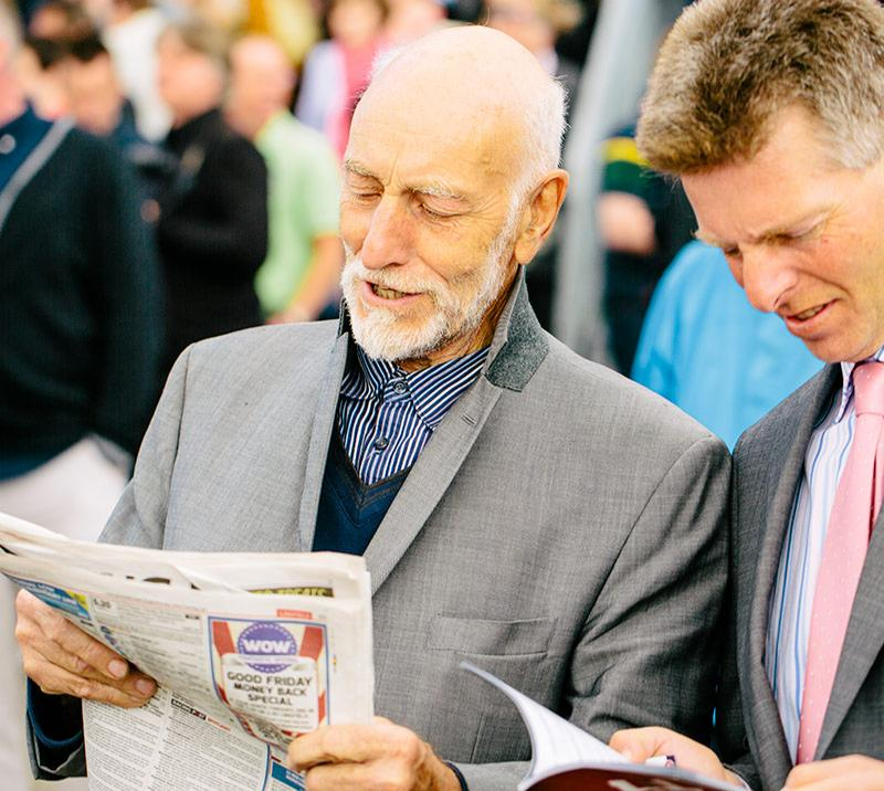 Two gentlemen reading through racing tips.