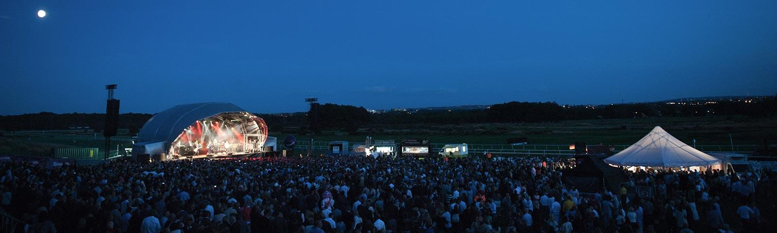 a crowd of people enjoying a live music concert at one of Arena Racing Company's venues