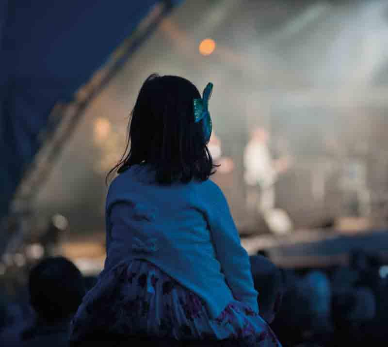 A young girl sits on her Fathers shoulders watching the acts on stage.