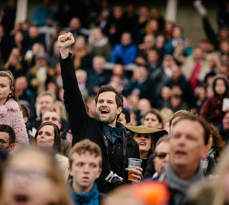 A man at the races cheering among the crowds.