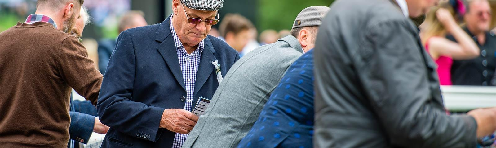 Group of gentlemen at the races, with one reading through a racecard.