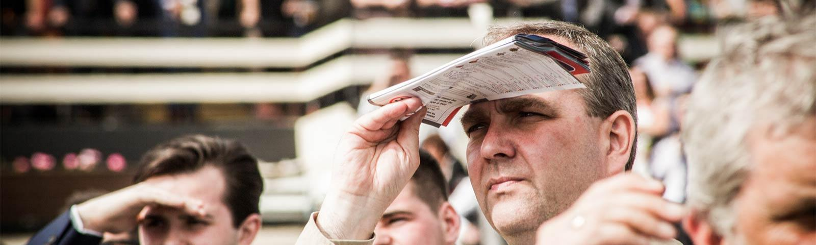 Gentleman shielding his eyes from the sun while watching racing.